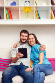 Couple sitting on sofa and holding the tablet pc — Stock Photo