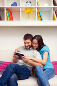 Couple sitting on sofa and looking at the tablet pc — Stock Photo
