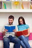 Couple sitting on sofa and reading books — Stock Photo