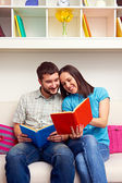 Couple sitting on sofa and reading the book — Stock Photo