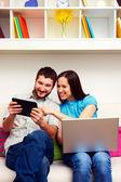 Happy couple sitting on sofa — Stock Photo