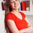 Woman posing over bookshelf — Stock Photo