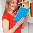 Woman reading the book and smiling — Stock Photo