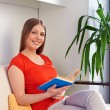 Woman sitting on couch and holding the book — Stockfoto