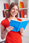 Young woman holding the book and smiling — Stock Photo