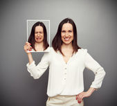 Happy woman holding her sad picture — Stockfoto