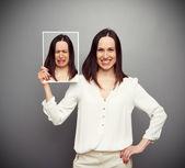 šťastná žena drží její smutný obrázek — Stock fotografie