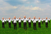 Happy crowd on the green field — Stock Photo