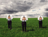 Faceless men standing on the green field — Stock Photo