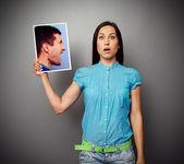Mujer sosteniendo la foto del hombre agresivo — Foto de Stock