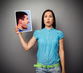 Woman holding photo of aggressive man — Photo