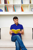 Man sitting on sofa and reading the book — Stock Photo