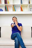 Man watching tv and yawning — Stock Photo