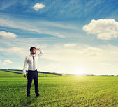 Thoughtful man standing on green field — Stock Photo