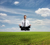 člověk vznášet nad zeleným polem — Stock fotografie