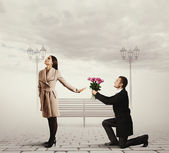 Woman rejecting man with flowers — Stock Photo