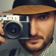 Stylish handsome man with camera — Stock fotografie