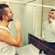 Stock Photo: Mbrushing teeth and looking at mirror