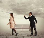 Man shaking fist at outgoing woman — Stockfoto