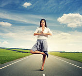 Woman in yoga pose standing on the road — Stok fotoğraf