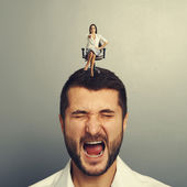 Earnest woman sitting on the screaming man — Stock Photo