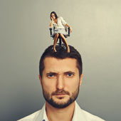 Woman sitting on the head of discontented man — Stock Photo