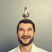 Woman sitting on the head of smiley man — Stockfoto