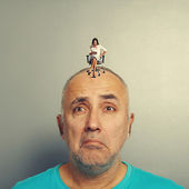 Sad man and small angry businesswoman — Stock Photo