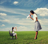 Two women with megaphone on the field — Stock Photo