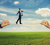 Assured businessman walking on the rope — Stock Photo
