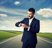 Man looking at his watch over road — Stock Photo
