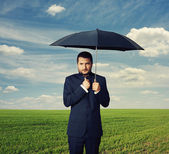 Man under black umbrella at outdoor — Stock Photo