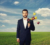 Man with faded flowers at outdoor — Foto Stock