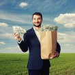Man holding paper bag with money — Stock Photo