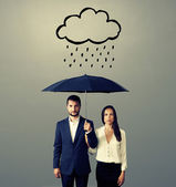 Serious couple with black umbrella — Stock Photo