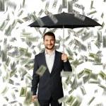 Man with umbrella standing under money rain — Stock Photo #49286953