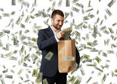 Businessman putting dollar's in the paper bag — Stock Photo