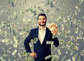 Happy businessman standing under money rain — Stock Photo