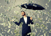 Man standing under money rain — Stock Photo