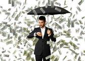 Man under money rain looking at watch — Stok fotoğraf