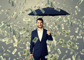Smiley and glad man under money rain — Stock Photo