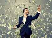 Smiley businessman catching money — Stock Photo