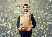 Smiley businessman holding paper bag with money — Stock Photo