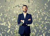 Smiley businessman under dollar's rain — Stock Photo