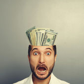 Shocked young businessman with money — Stock Photo