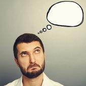 Perplexed man looking at speech bubble — Stock Photo