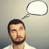 Perplexed man looking at speech bubble — Stock Photo