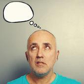 Senior man looking at empty speech balloon — Stock Photo