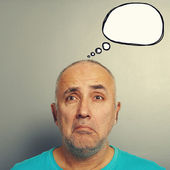 Sorrowful senior man with white speech balloon — Stockfoto