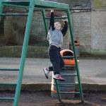 Young boy climbing on monkey bars — Stock Photo #43169705
